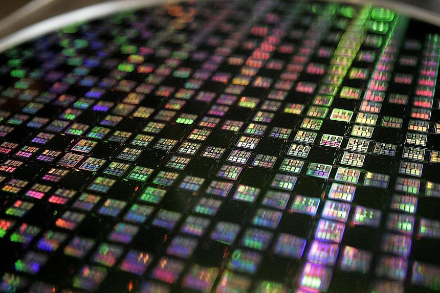 A wafer at TSMC, the world's biggest contract chipmaker. The company, which supplies some of the chips that go into the iPhone, says first-quarter revenues will likely fall by up to 11 per cent year-on-year.