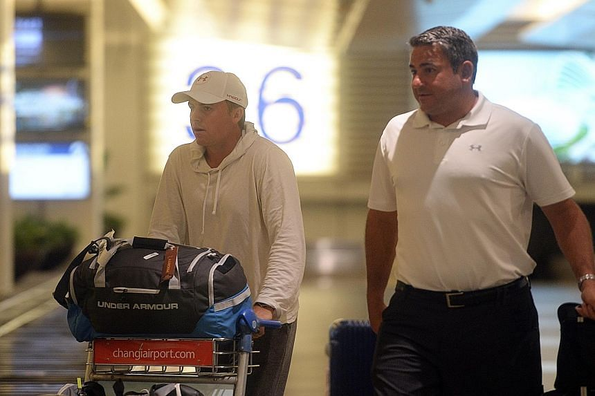 Jordan Spieth (left) and manager Jay Danzi arriving at Changi Airport yesterday morning. His punishing schedule could see him log 200,000km in 11 months if he makes the Olympics.