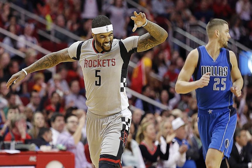 Back with Houston after half a season with the LA Clippers, Josh Smith is delighted after making a three-pointer, as Dallas forward Chandler Parsons runs back for the re-start. The Rockets won 115-104.
