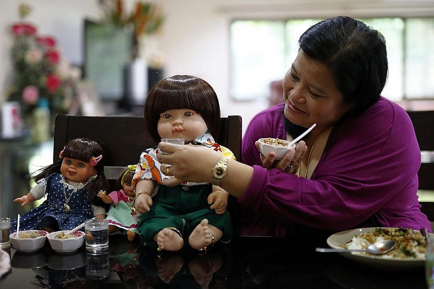A Thai devotee feeding her child angel doll. Some Thais believe these dolls hold children's spirits, which bring good luck, wealth, blessing and protection from harm if they are well cared for.