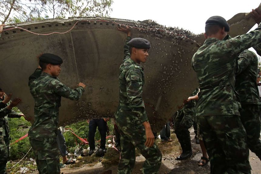 Thai soldiers carry a piece of suspected aircraft debris at a beach in the southern province of Nakhon Si Thammarat on Jan 25, 2016.