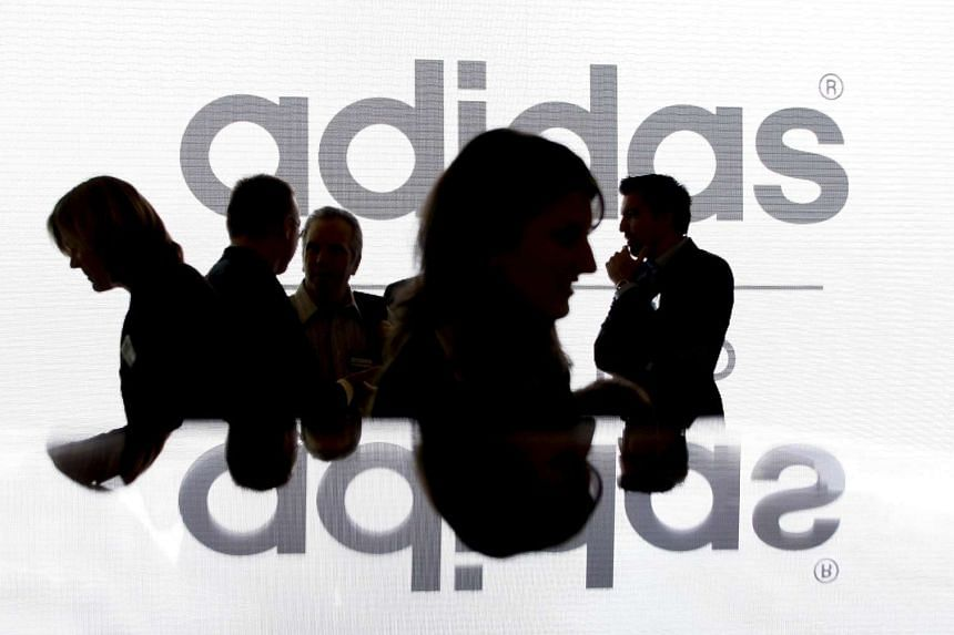 Shareholders of Adidas Group are silhouetted in front of the company logo before the annual shareholder meeting in Fuerth near Nuremberg.
