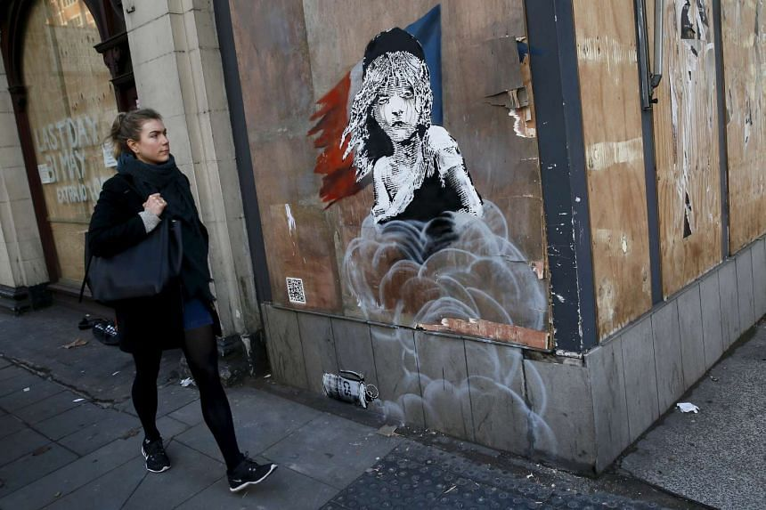 A woman walks past a new graffiti mural attributed to Banksy, opposite the French embassy in London on Monday.