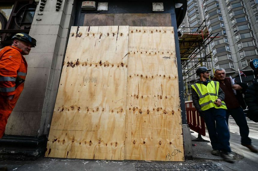 A man walks past sheets of wood covering the mural by British graffiti artist Banksy on Monday.