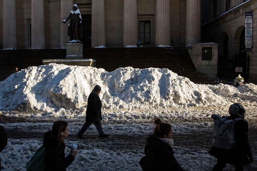 People walk past wall of snow on Wall Street  on Monday in New York City.