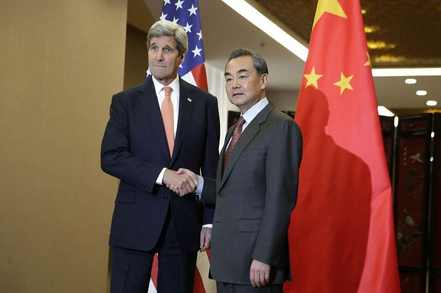 US Secretary of State John Kerry (left) shakes hands with Chinese Foreign Minister Wang Yi before their bilateral meeting at the Ministry of Foreign Affairs in Beijing, on Jan 27, 2016.