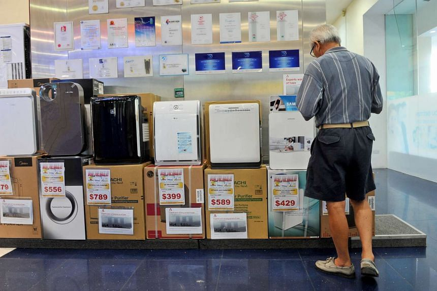 A man looking at different models of air purifiers in 2014.