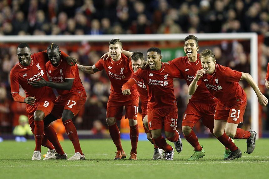 Liverpool players celebrate after Joe Allen (not pictured) scores the penalty to win the penalty shootout against Stoke City in the League Cup semi-final.