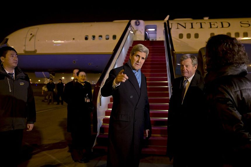US Secretary of State John Kerry (centre) is greeted by US Ambassador to China Max Baucus, on his arrival in Beijing on Jan 26, 2016.