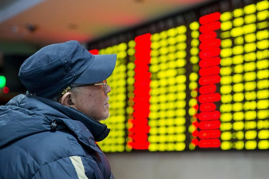 An investor looks at an electronic screen showing stock information at a brokerage house in Nanjing, Jiangsu province, on Jan 26, 2016.