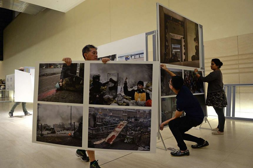 Mr Herbert Ho, head of operations at Sphere Exhibits Pte Ltd, helps set up the World Press Photo 2015 exhibition at the National Museum of Singapore on Jan 26, 2016.