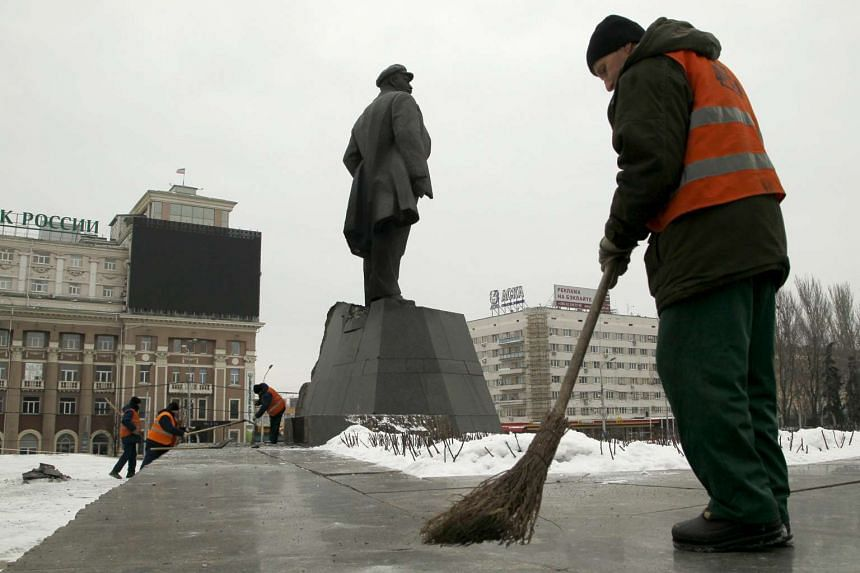 Sweepers clean a street near a monument of the Soviet state founder Vladimir Lenin on Jan 27, 2016.
