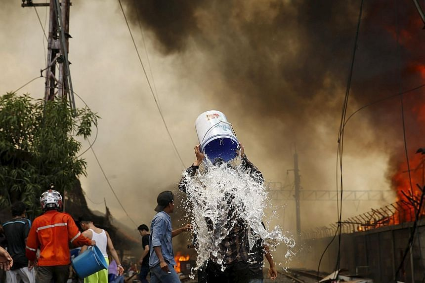 A man dousing himself with water during a fire in a slum area next to railway tracks in Kampung Muka, Kampung Bandan, North Jakarta, yesterday. According to local media, the fire destroyed about 100 wooden dwellings built along a busy railway line. A