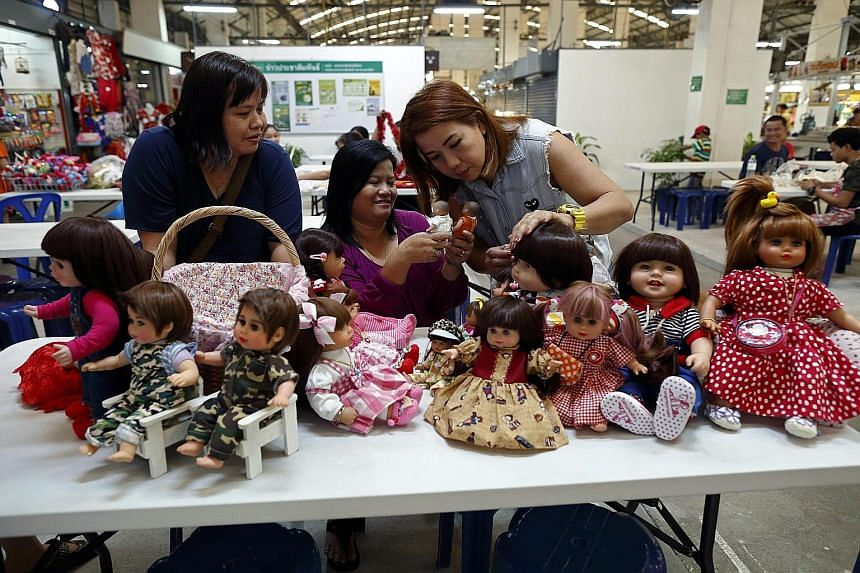 """Known in Thai as """"luk thep"""" (child angels), the dolls, which can cost up to US$600, were popularised by celebrities who claimed that dressing up and feeding the dolls had brought them professional success."""