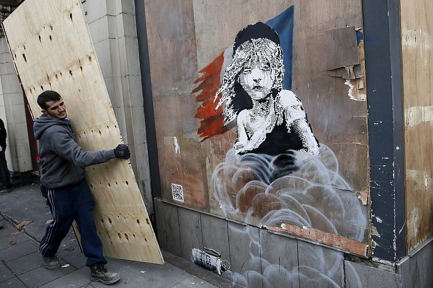 "A worker about to cover a new mural, attributed to graffiti artist Banksy, opposite the French Embassy in London. The mural highlights the alleged use of tear gas on migrants at the ""jungle"" camp in Calais, and comes amid calls in Britain to take in"