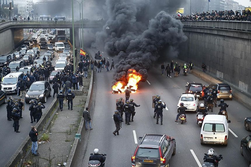 Anti-riot policemen dispersing taxi drivers and putting out burning tyres (above) on the ringroad around Paris yesterday. The taxi drivers also blocked traffic (below) in other parts of France as part of a national protest against competition from pr