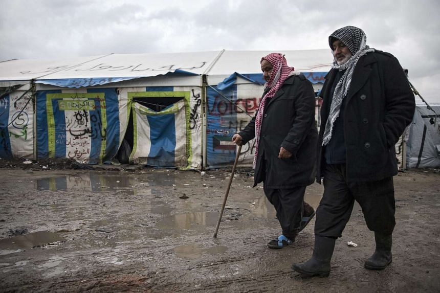 """Khaled and Rauf, migrants from Kuwait, walk back to the shack they share with several Kuwaitis in the Calais """"Jungle"""" camp."""