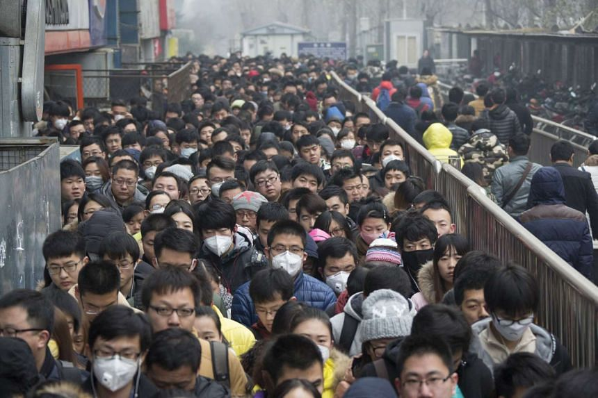 Morning commuters wait in line at the Tiantongyuan subway station on a smoggy day.