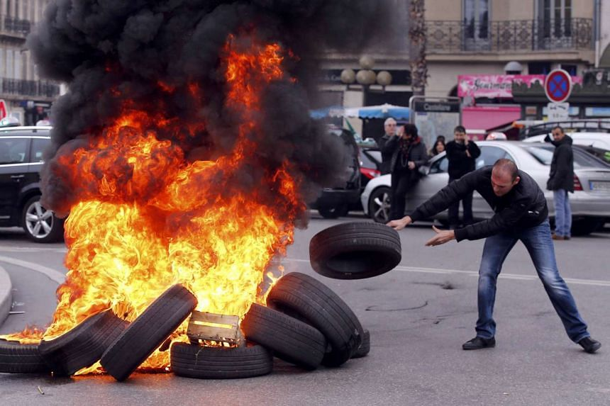 A striking French taxi driver burns tyres during a national protest about competition from private car ride firms like Uber.