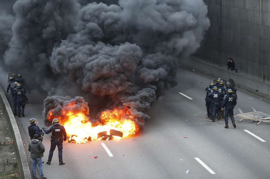 Anti-riot police stand next to a fire during the taxi drivers demonstration.