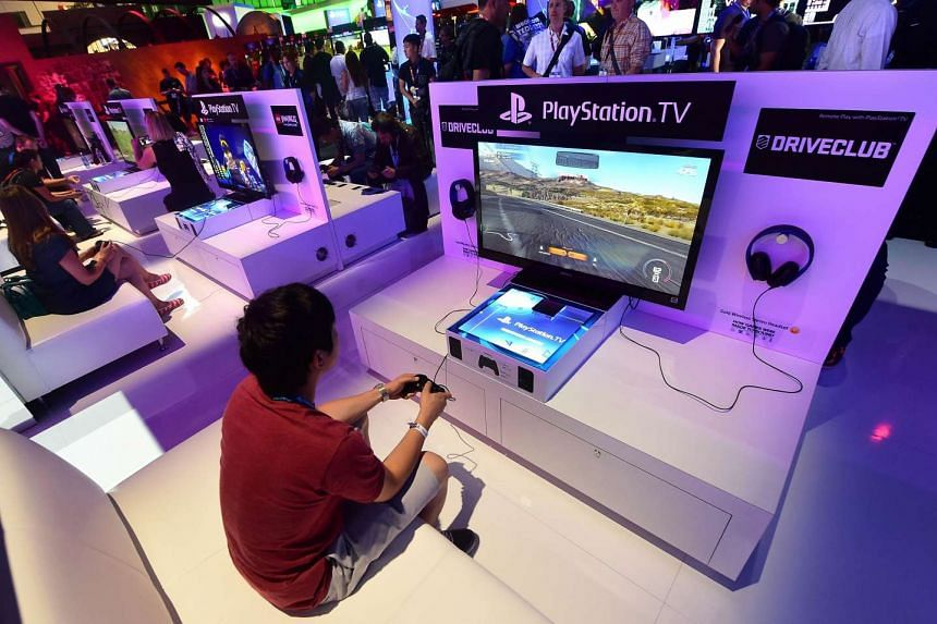A 2014 file photo shows people trying out PlayStation TV consoles.