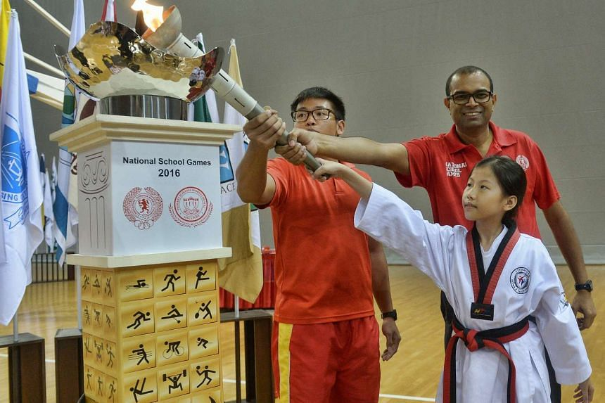Minister of State for Education Janil Puthucheary (second from right) lighting the cauldron with torch bearers Almanda Mik (right) and Eric Yee, on Jan 28, 2016.