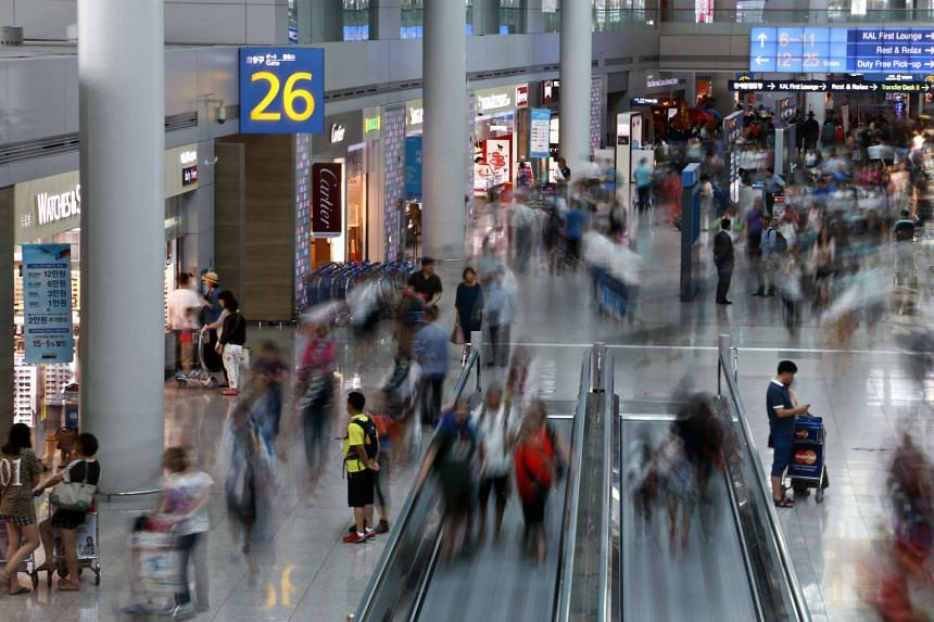 Travelers move through the duty free shopping area at Incheon International Airport in South Korea.