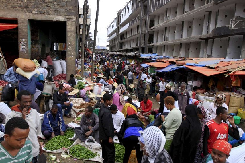 People buy vegetables at a market in Addis Ababa, Ethiopia.