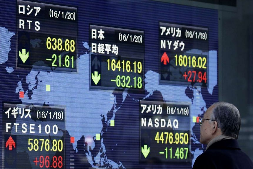 A pedestrian looks at an electronic stock board outside a securities firm in Tokyo.