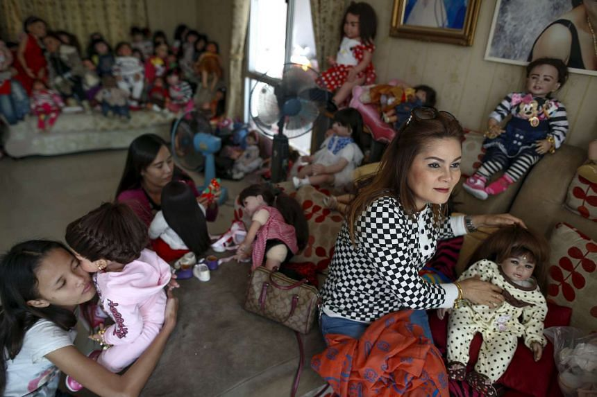 Devotees play with child angel dolls at a house in Nonthaburi, Thailand.