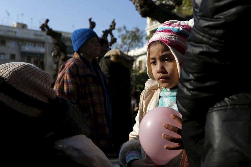 A migrant child holding a balloon in Victoria Square, Greece, on Jan 27.