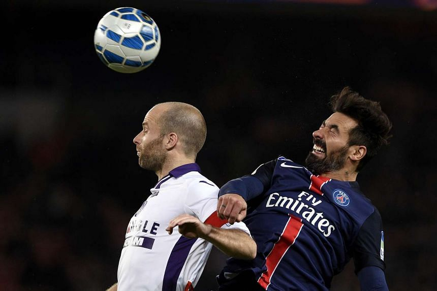 Paris Saint-Germain's Ezequiel Lavezzi (right) and Toulouse's Etienne Didot go for a header during their French League Cup football match.