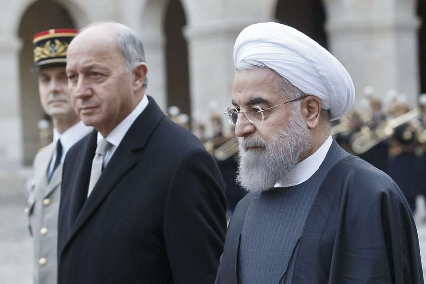 French Foreign Minister Laurent Fabius and Iranian President Hassan Rouhani inspecting the honour guards.
