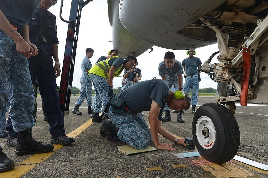 An assessor measures the accuracy of the precision marshaller in stopping the F-16 on its mark as the aircraft comes in to park at the Tengah Air Base after a mission.
