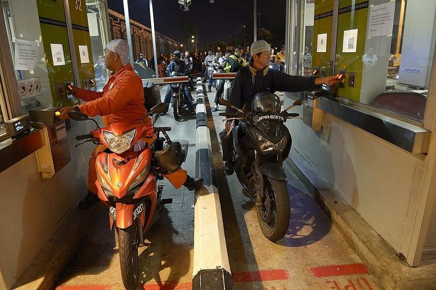 Motorcyclists bound for Singapore scanning their fingerprints while going through the automated clearance channels at Woodlands Checkpoint. Senior Minister of State for Home Affairs Desmond Lee noted that more than half a million people pass through
