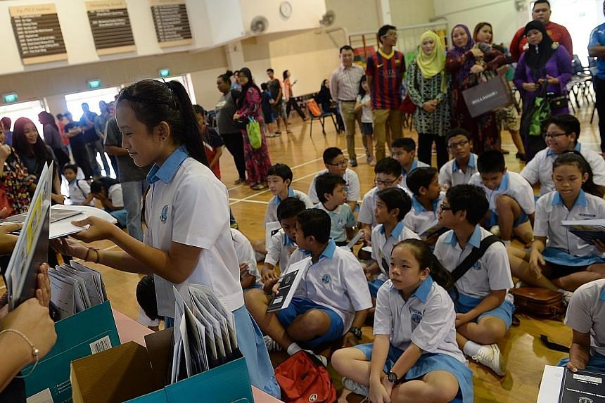 Eunos Primary School pupils receiving their PSLE results last year. Yesterday, Ms Denise Phua renewed her call for the Education Ministry to pilot a 10-year through-train school model - with children moving from the primary to secondary level without