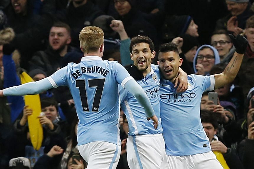 Sergio Aguero celebrates with team mates after scoring the third goal for Manchester City.