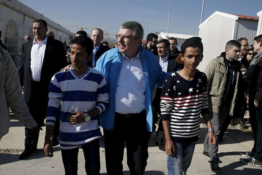 Thomas Bach (centre) walking with migrants at the Eleonas refugee camp in Athens, Greece, on Jan 28, 2016.