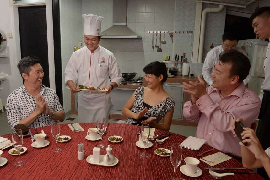 Chef Chen serving appetiser to Mr and Mrs Quek Ser Wee (both above). He also gave them autographed copies of his cookbook, Chef's Family Recipes.
