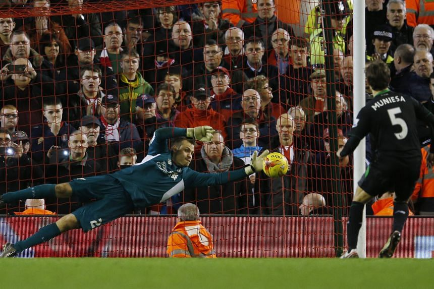Liverpool's Joe Allen scoring the decisive penalty to win the shoot-out (6-5) against Stoke City in their League Cup semi-final second leg. Reds goalkeeper Simon Mignolet (above) also played a crucial role, saving from Peter Crouch and Marc Muniesa in the