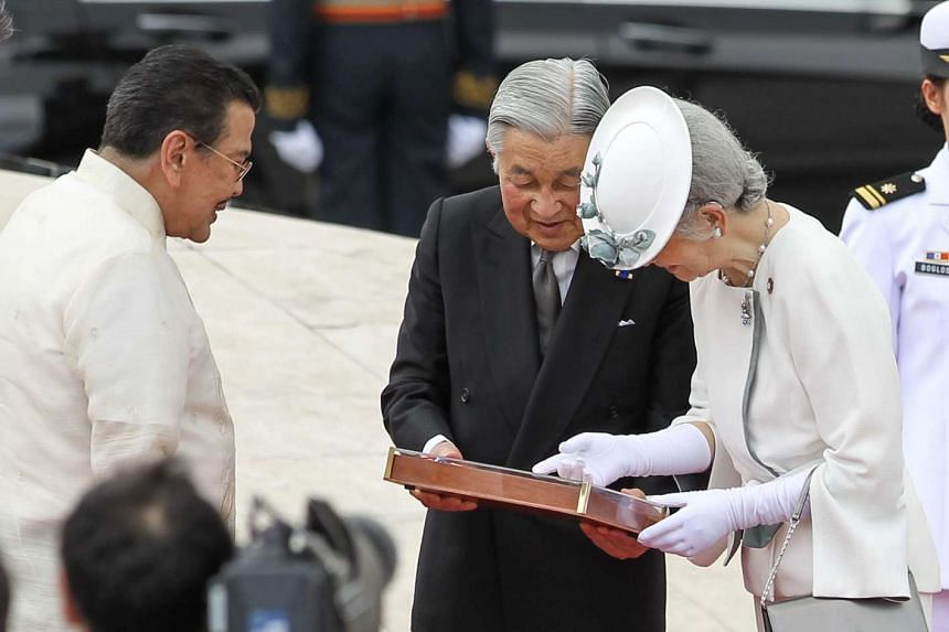 Japan's Emperor Akihito and Empress Michiko admiring their gift from former Philippine president and now Manila mayor Joseph Estrada during a wreath-laying ceremony at the monument of Philippine national hero Jose Rizal in the Luneta Park in Manila y