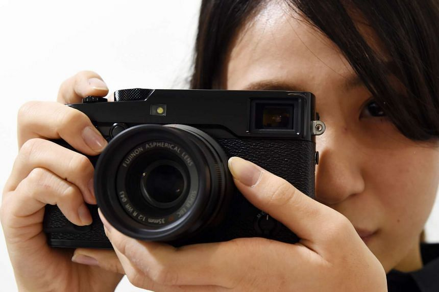 A Fujifilm employee poses with the company's new X-Pro2 premium mirrorless digital camera.