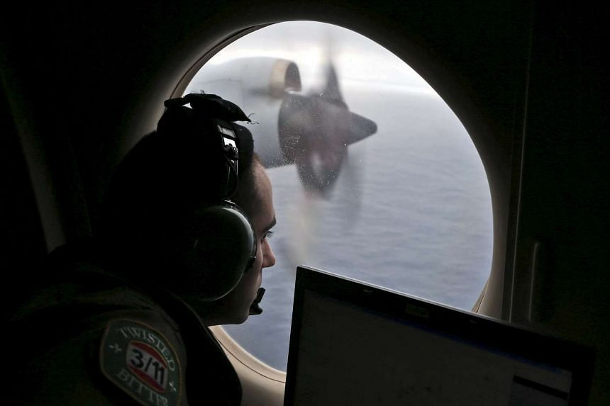 Flight officer Rayan Gharazeddine looking out of a Royal Australian Air Force AP-3C Orion during the search for the missing flight MH370 in this March 22, 2014 file photo.