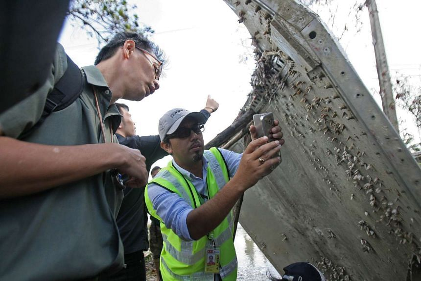 A Malaysian official takes pictures of a piece of suspected aircraft debris in Nakhon Si Thammarat on Jan 25, 2016.
