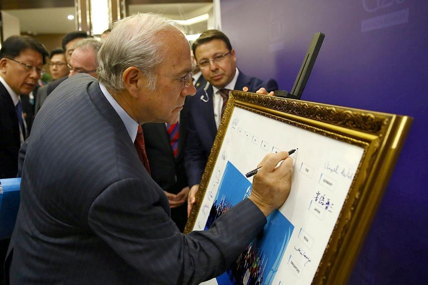 OECD Mexican Secretary-General Angel Gurria signing a print of the G20-Turkey family photo at the G20 summit on Nov 15, 2015.