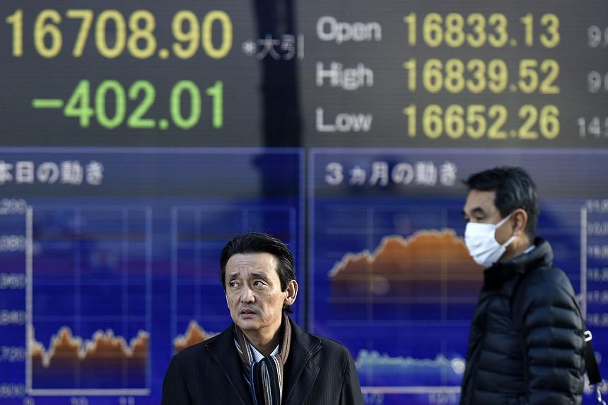 Pedestrians in front of a stock market indicator board in Tokyo on Jan 26.