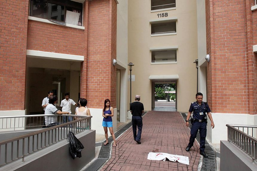 Police and residents at the foot of a block in Yishun, where a cat was found dead, on Oct 30, 2015.