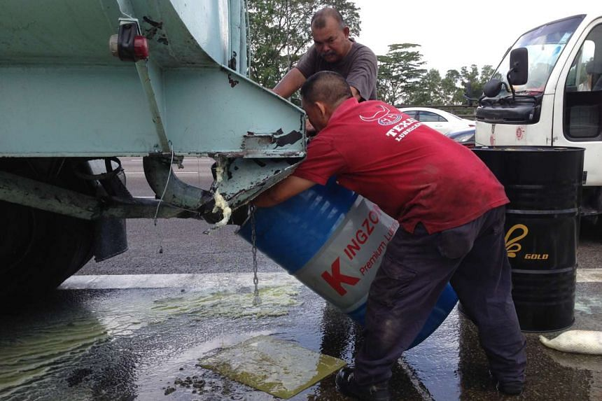 Workers attempting to catch oil flowing out of a truck along the BKE.