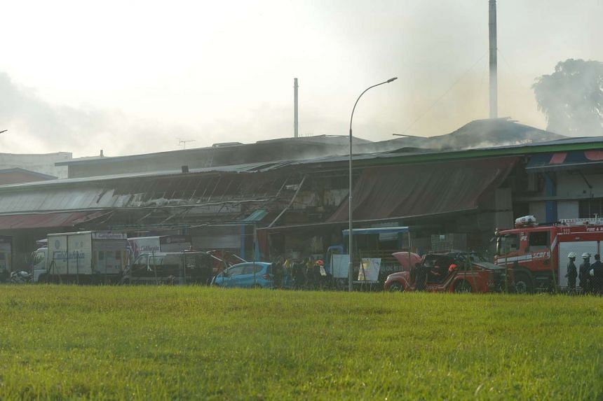 SCDF firefighters during the damping down operations on Friday morning.