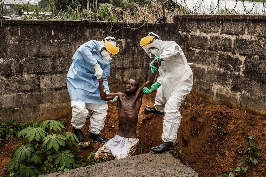 Medical staff at Hastings Ebola Treatment Center escorting a man in the throes of Ebola- induced delirium back to the isolation ward. He died shortly after photographer Pete Muller took this award- winning picture.